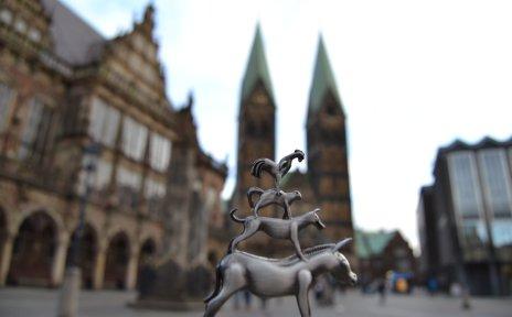 Die Bremer Stadtmusikanten als Souvenir mit dem verschwommenen Dom im Hintergrund.