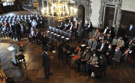 Personen sitzen in Stuhlreihen in einem festlichen Saal.
