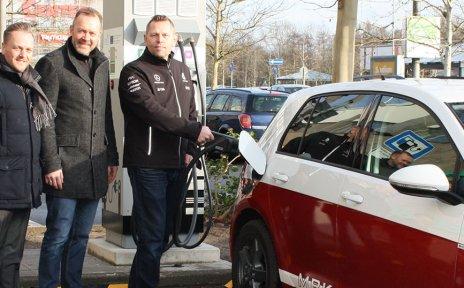 Ein Elektroauto steht auf einem Parkplatz vor einer E-Ladesäule. Drei Männer stehen neben dem Auto, einer von ihnen lädt das Auto.