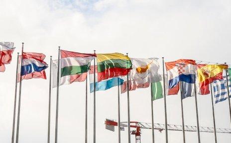 Bunte Flaggen europäischer Nationen vor blauem Himmel