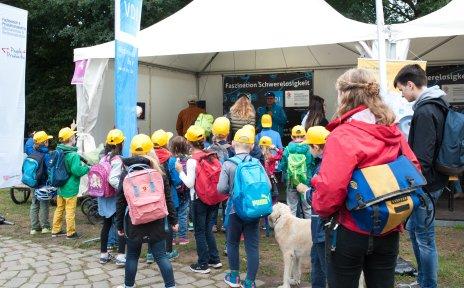 Eine Gruppe Kinder mit gelben Capys steht vor einem der Infozelte über Schwerelosigkeit.