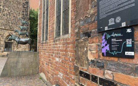 Ein Schild mit einem QR-Code hängt an der Wand des Rathauses. Im Hintergrund stehen die Stadtmusikanten.