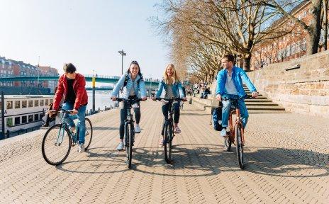 Junge Menschen fahren am Deich Fahrrad
