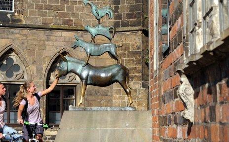 Zwei Fahrradfahrer und die Statue der Bremer Stadtmusikanten