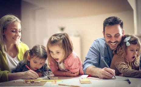 Eine Frau, ein Mann und drei kleine Mädchen malen und schreiben gemeinsam.