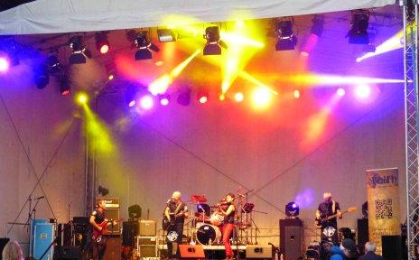 Eine Band steht auf einer großen und bunt beleuchteten Bühne.