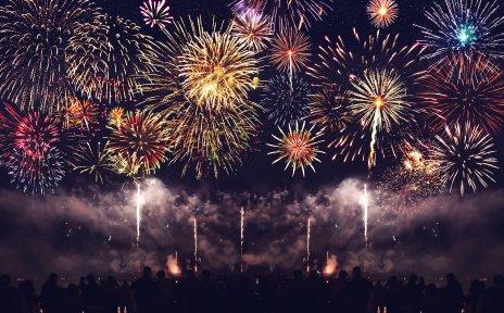 Zahlreiche Menschen, der Umrisse man am unteren Bildende erkennen kann, bestaunen ein buntes Feuerwerk am nächtlichen Himmel.