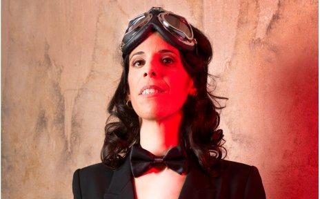 Eine Schauspielerin, die komplett in schwarz gekleidet ist auf rotem Hintergrund.