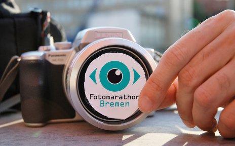 Eine Hand hält das Logo des Fotomarathons vor ein Kameraobjektiv; Quelle: Fotomarathon Bremen/Kerstin Graf