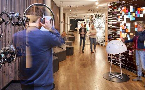 Mehrere Menschen stehen in einer Ausstellung und haben Kopfhörer auf.