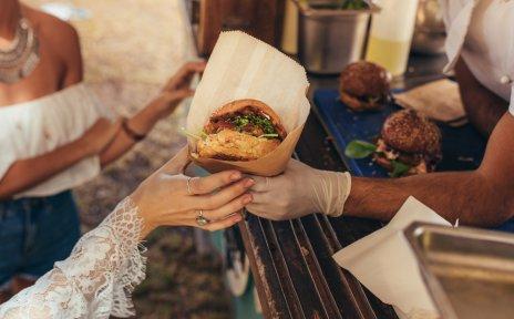 An einem Foodtruck wird einer Kundin ein Burger gereicht