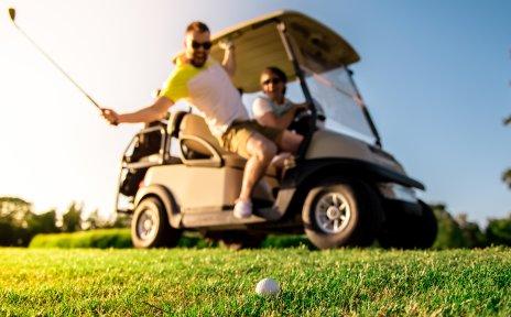 Zwei Männer sitzen in einem Golfcart und schlagen einen Ball.