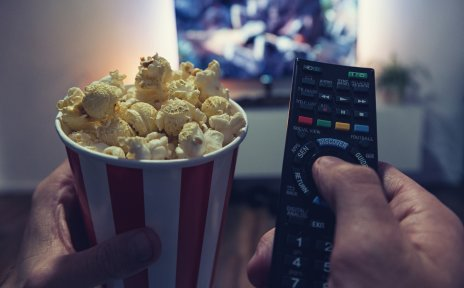 Eine Person sitzt vor einem Fernseher und hält eine Fernbedienung und einen Becher Popcorn in der Hand