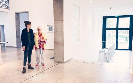 Zwei Frauen stehen nebeneinander in einem Gebäude. Eine von ihnen hält einen Langstock in der Hand.