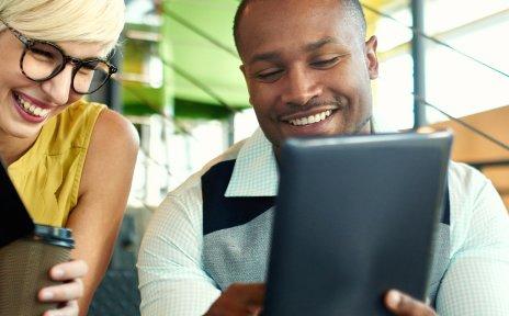 Zwei lachende Personen, eine Frau und ein Mann, sitzen auf einer Treppe. Sie hat ein Notizbuch in der Hand, er zeigt etwas auf einem Tablet.