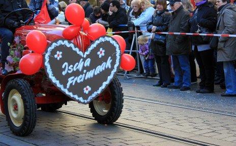 Ein buntes Lebkuchenherz aus Pappe hängt an einem roten Traktor.