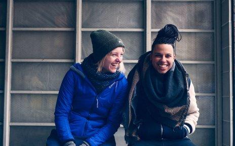 Zwei lachende junge Frauen sitzen nebeneinander.
