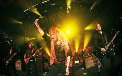 Die Band Galatic Superlords steht auf der Bühne. Die Frontfrau hält ein Mikrofon in die Luft.