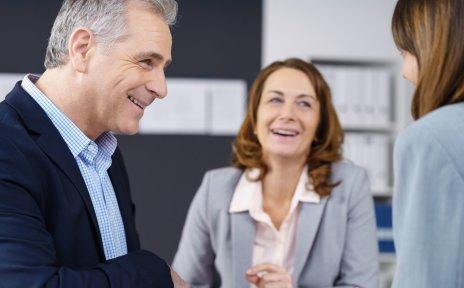 Zwei Frauen und ein Mann lachend in einem Geschäftsgespräch (Quelle: fotolia / contrastwerkstatt)