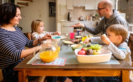 Ein Mann und eine Frau sitzen mit zwei kleinen Kindern am Frühstückstisch. Ein Bild über den Alltag in einer Familie mit behinderten und nicht behinderten Kindern.