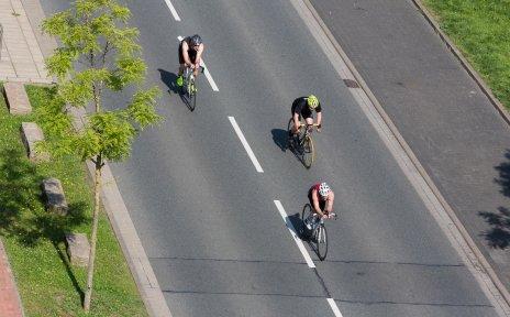 Triathlon-Teilnehmer fahren auf Fahrrädern über die Straße.