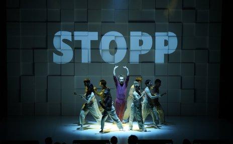Zu sehen sind Künstler*innen der Show Sombra. Sie stehen in einem Kreis, dem Publikum zugewandt. Im Hintergrund steht auf einer Leinwand das Wort Stopp in Großbuchstaben.