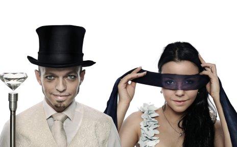 Zu sehen sind ist ein Pärchen. Der Mann trägt einen Zylinder und die Frau hält sich eine Augenbinde vor das Gesicht.