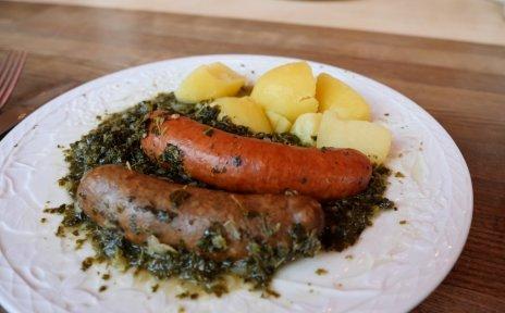 Ein weißer Teller, auf dem Grünkohl, Kartoffeln, Pinkel und Kochwurst liegen.