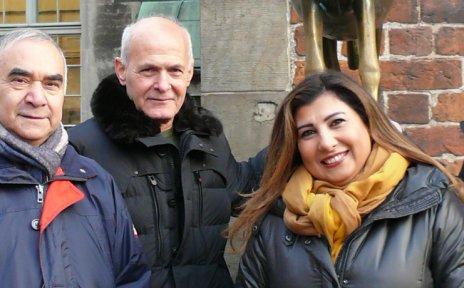 Die Einbürgerungslots*innen stehen vor den Bremer Stadtmusikanten und lächeln in die Kamera.