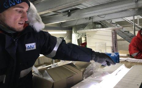 Ein Mann in Winterkleidung vor einer leuchtenden Röhre mit Eis