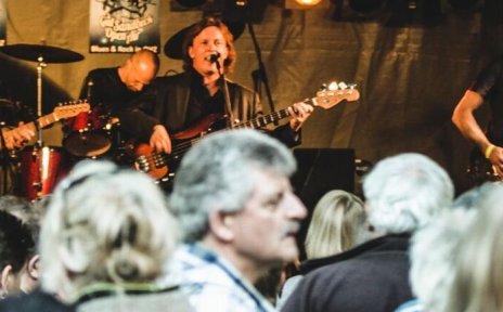Eine dreiköpfige Band spielt auf einer Bühne vor Publikum.