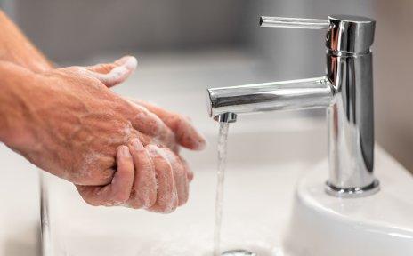 Zwei eingeseifte Hände an einem Waschbecken und ein Wasserhahn, aus dem Wasser läuft.