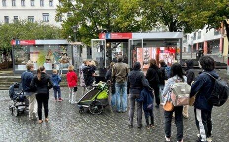 Glascontainer werden als Veranstaltungsbühnen für Konzerte genutzt, davor steht Publikum und schaut zu.