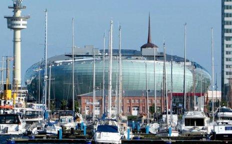 Ein hohes Gebäude und ein rundes Gebäude am Wasser