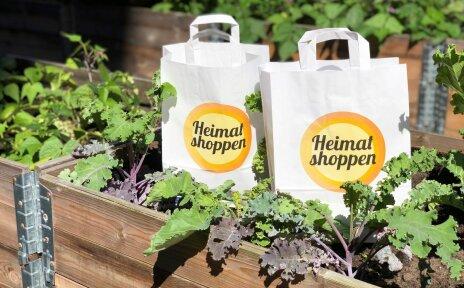"""Man sieht zwei Papiertüten mit dem Logo der Aktion """"Heimat Shoppen"""", die in einem Beet stehen."""