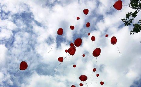 Rote Herzen steigen in den blauen Himmel