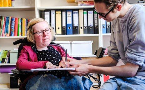 Eine Frau sitzt in einem Rollstuhl mit Rollstuhltisch. Neben ihr sitzt ein Mann und scvhreibt etwas auf ein Papier, das auf dem Rollstuhltisch liegt. Im HIntergrund sind Regale mit Aktenordnern und Büchern zu sehen.