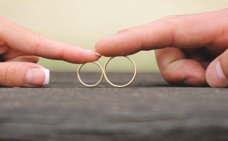Ein Paar schiebt sich gegenseitig die Ringe zu