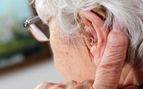 Seitliche Aufnahme einer Seniorin. Sie trägt ein Hörgerät und eine Brille.