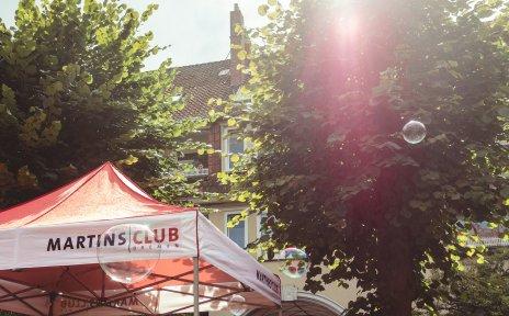 """Hinter zwei Bäumen ist ein Teil einer Hausfassade zu sehen. Im vorderen Teil des Bildes steht ein Pavillon mit der Aufschrift """"Martinsclub Bremen""""."""