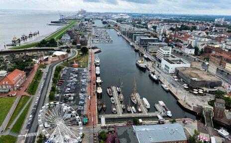 Das Hafenbecken in Bremerhaven von oben. Es liegen Boote im Becken. Am Rand steht ein Riesenrad.