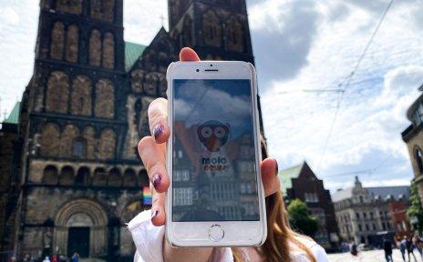 Eine Frau hält ein Handy in die Kamera. Im Hintergrund ist der Bremer Dom zu sehen.