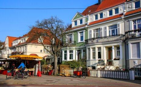 Vor drei bunten alten Häusern stehen zwei Wochenmarktstände und ein Mann hält dort mit einem Fahrrad.