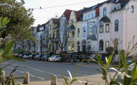 Der Blick fällt auf eine Reihe Altbremer Häuser. Davor parken Autos und es hängen Zweige im Bild.