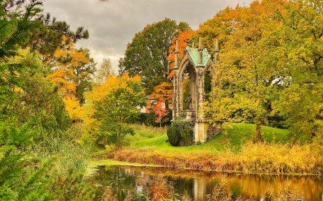 Herbstlich verfärbte Bäume umranken ein Grabmonument und ein Gewässer auf dem Waller Friedhof