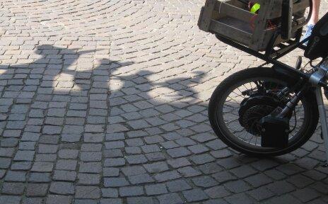 Vorderreifen eines Handbikes. Der Boden ist mit Kopfsteinpflaster versehen, man sieht einen Schatten der Bremer Stadtmusikanten.