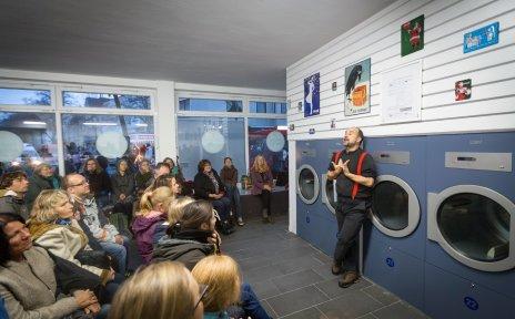 Ein Mann erzählt vor Publikum in einem Waschsalon.