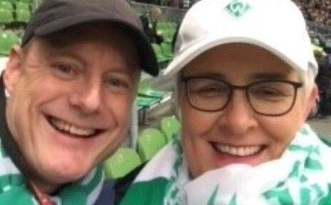Eine Frau und ein Mann im Fußballstadion.
