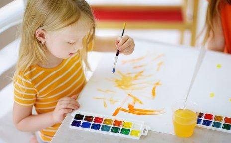Ein kleines Mädchen sitzt am Tisch und malt ein Bild mit gelber Farbe.