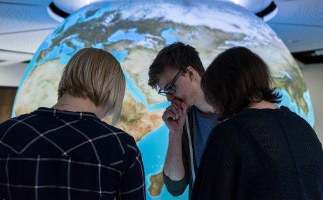 Drei Schüler vor einer Weltkugel im Klimahaus